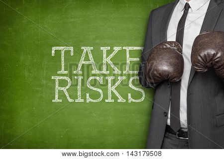 Take risks on blackboard with businessman wearing boxing gloves