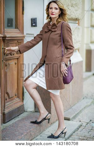 Beautiful middleaged woman in jacket opens old door, shallow dof