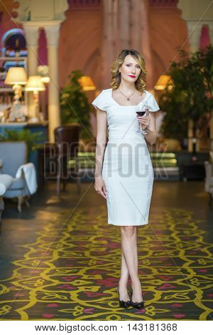 Middleaged woman in white dress stands with wine in restaurant, shallow dof