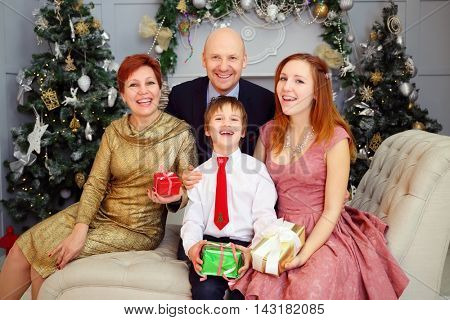Mother, father, son and daughter sit on couch with gifts during christmas