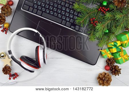 Listen to Christmas music. Congratulate your friends and family online. Modern methods of communication. Technology helps to keep in touch. Headphones and Computer peripherals Christmas tinsel and gifts on wooden background. top view. Christmas tree and g