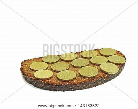 Euro cent coins on black bread. Isolated on white background.