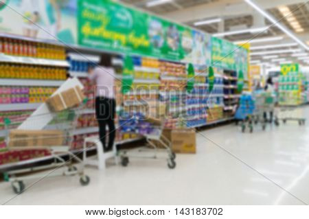 Merchandising. Sales assistant in supermarket arrange goods on supermarket shelves at store Abstract Blur or Defocus Background