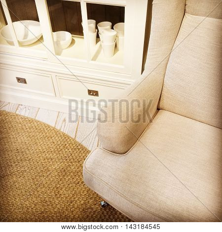 Detail of a living room with armchair white sideboard and woven rug.