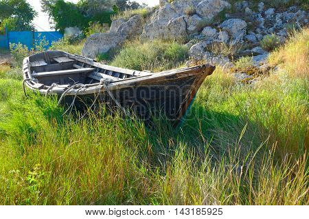 Old fishing boat on the land in tall grass in front of gates painted in blue and rock