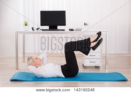 Young Businesswoman Exercising On Exercise Mat In Office