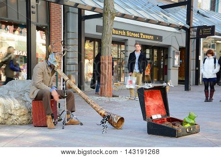BURLINGTON, VT, USA - APR 6, 2013: Street Artist playing African Horn at Church Street Marketplace in downtown Burlington, Vermont, USA.