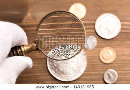 Examining old silver coin through magnifying glass on wooden table