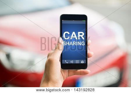Close-up Of A Person Hand Holding Smart Phone Showing Car Sharing App On Screen