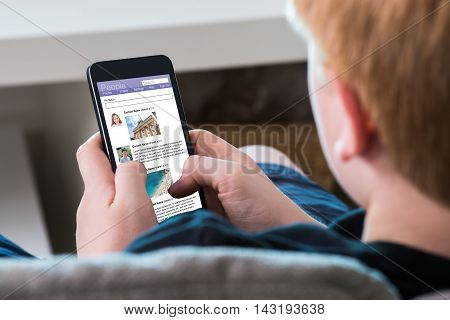 Close-up Of A Boy Using Social Networking Site On Mobile Phone