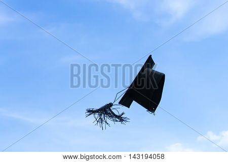 One graduation cap or mortar board thrown up to the air sky background