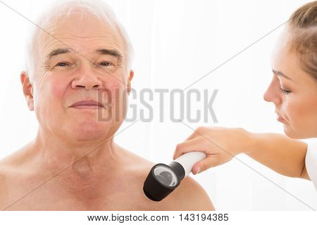 Young Female Doctor Examining Skin Of Senior Male Patient With Dermatoscope