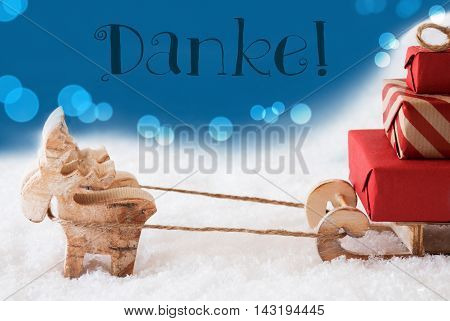Moose Is Drawing A Sled With Red Gifts Or Presents In Snow. Christmas Card For Seasons Greetings. Blue Background With Bokeh Effect. German Text Danke Means Thank You