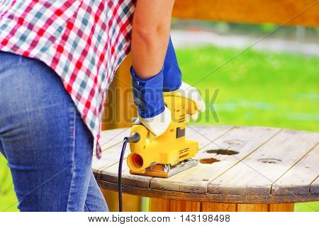 woman sanding a wood table with a yellow electric sander.