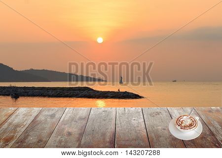 Morning coffee on wood table at sunset or sunrise sea The delicious aroma Cappuccino coffee : space for text and may be used as background :