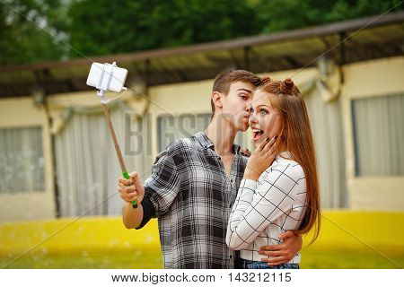 Enamoured teenagers do selfie. Girlfriend and boyfriend strolling in a city park. Boy holding a selfie stick with a smartphone and hugs girl. First love. He falls in love. Date.