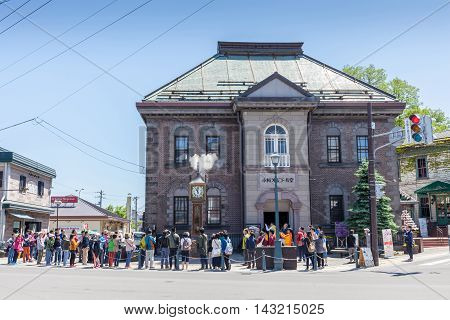 Otaru Hokkaido Japan- June 5 2016. Tourists visited the vintage steam clock tower in front of Otaru Music Box Museum. The steam clock was made by Canadian clock maker Raymond Sounders in 1977.