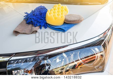 Yellow green sponges and blue mitts for washing and microfiber fabric with cleaner cloth on white car