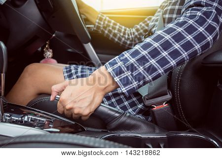 Closeup of young woman pulling handbrake lever in car