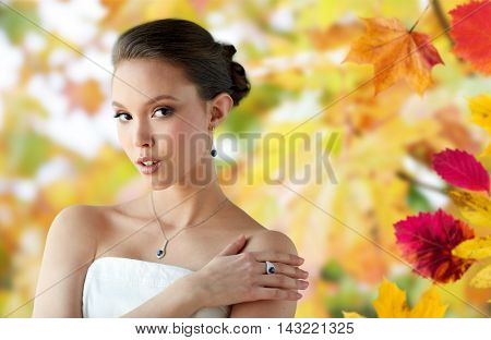 beauty, jewelry, people and luxury concept - beautiful asian woman or bride with earring, finger ring and pendant over autumn leaves background