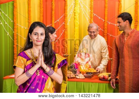 indian young women or young girl in prayer position facing camera in ganpati festival or ganesh festival