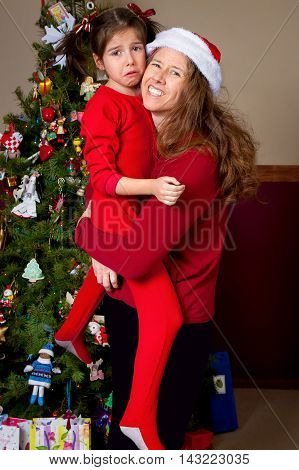 A mother stands smiling for the camera as her daughter whom she is holding pouts and cries. They are in red and in front of a Christmas tree.