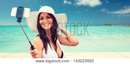 lifestyle, leisure, summer, technology and people concept - smiling young woman or teenage girl in sun hat taking picture with smartphone on selfie stick over tropical beach background