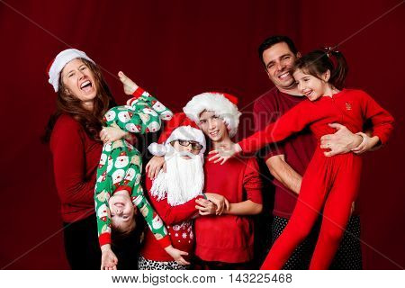 A silly family poses in a funny way for a Christmas portrait. The mom laughs and holds her son upside down one girl is wearing a Santa hat and beard while hugging her sister while the dad holds another daughter who reaches out to her sisters.