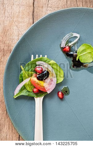 Spinach and Pomegranate salad on yellow fork on with Balsamic dressing