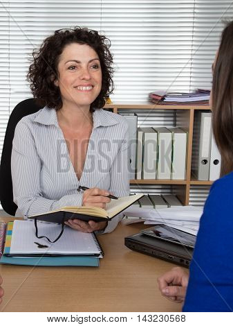 Woman receptionist and personal assistant is very serious. She is taking notices as a business woman