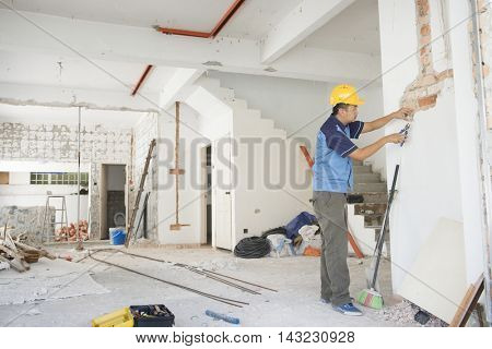 House renovation concept. Asian construction worker with hardhat working.