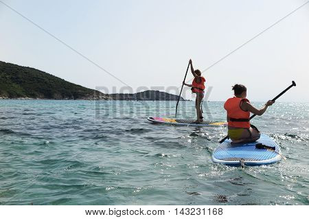 Beautiful and happy young girl learning paddle-surf