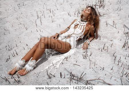 Attractive wild boho woman lying on sand