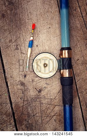 Fishing rod with reel a float sinker and hook on a wooden background retro filter