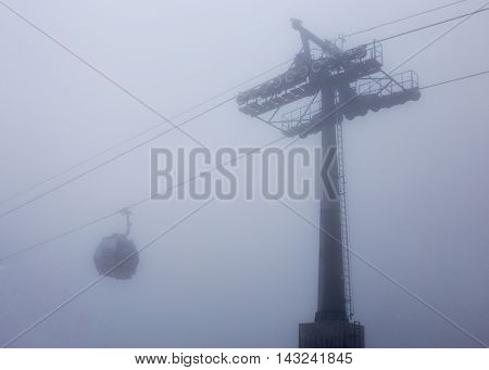 cable way with cabin car in deep mist white background