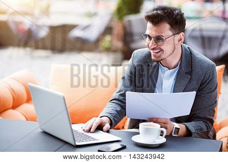 Enticed in work. Positive handsome smiling businessman sitting in the cafe and working with papers while suing laptop