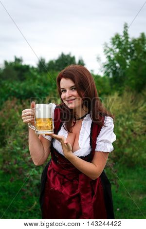 Beautiful, young, Bavarian woman in dirndl with beer