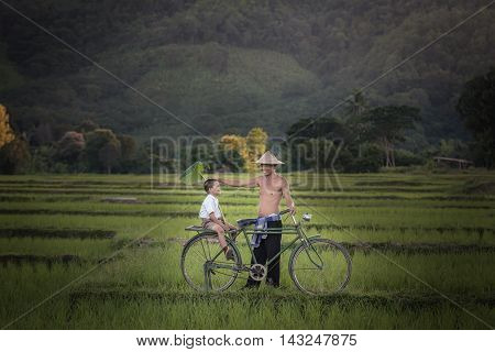 Father and sun with bicycle in rural Thailand.