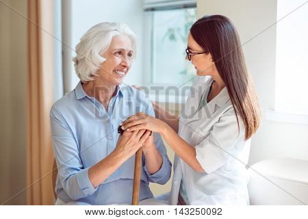 Graying population. Happy and cheerful senior woman with her young content nurse