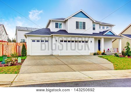 Luxury Two Level House Exterior With Garage And Concrete Driveway.