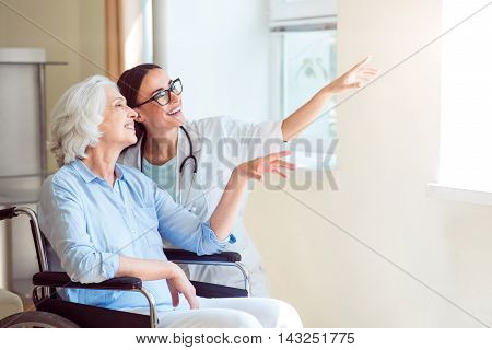 Dream big. Young nurse pointing somewhere with old disabled female patient in wheelchair