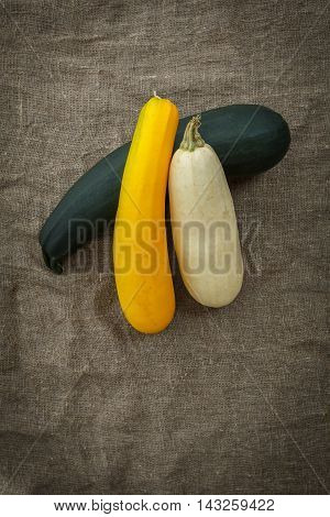 Fresh zucchini or marrow squash or courgette on rustic burlap background. Vegetables in different shapes and colors concept of diversity top view