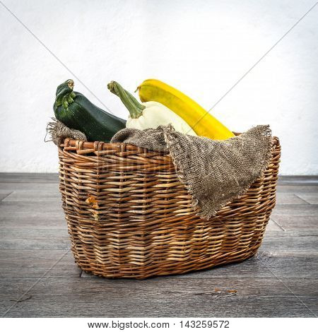Fresh zucchini or marrow squash or courgette in basket on burlap against wooden background. Vegetables in different shapes and colors concept of diversity