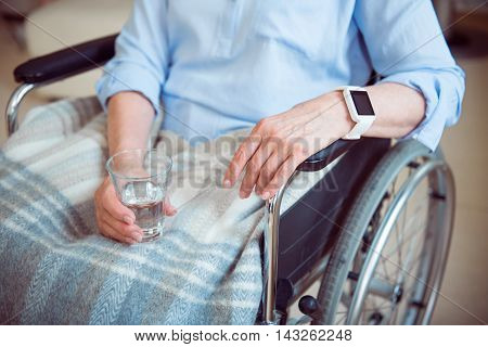 Disabled patient. Cropped image of senior woman in wheelchair holding glass of water