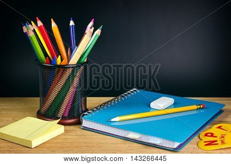 Teacher's desk with a color pencil, notebook and other equipment. Back to school concept