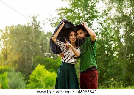 Beautiful Pair Of Lovers Hiding From The Rain Under His Jacket While Walking
