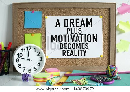 Motivation concept motivational quote on bulletin board in office / A dream plus motivation becomes reality