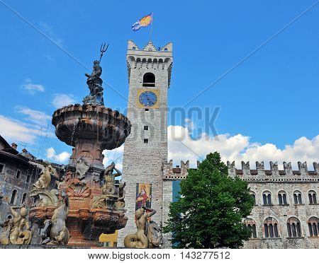 Old tower and fountain sculpture of Trento cathedral square Italy