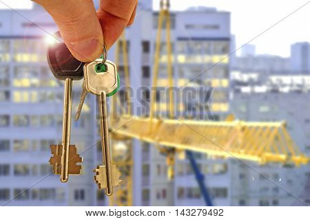 The keys to the apartment in the background of a house . The concept of the popularity of new housing .