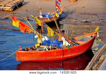 Bang Saen Thailand - January 10 2014: Tbai fisherman working in his small skiff moored next to the Bang Saen Sapan Pla fishing pier *